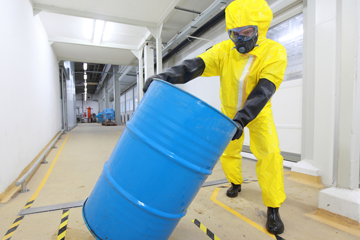 Employee in PPE moving chemical drum