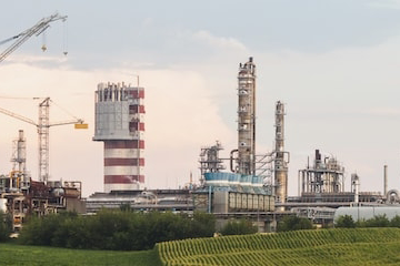 image of fertilizer factory with green field in front against a sunrise sky