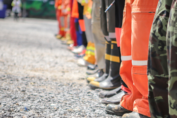 Legs of various emergency workers in uniform and PPE