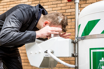 Male worker in  boiler suit uses eye wash, leaning over it and holding his eyes open with his fingers