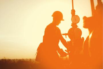 Worker in hard hat on oil field, silhouetted against an orange sky