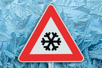 Warning road sign with snowflake symbol in front of frosty background